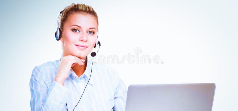 Stående av den härliga affärskvinnan som arbetar på hennes skrivbord med hörlurar med mikrofon och bärbara datorn royaltyfri bild