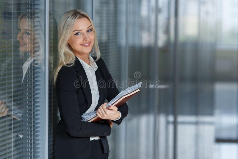 Stående av den härliga affärskvinnan som ler och står med mappen i kontoret royaltyfri bild