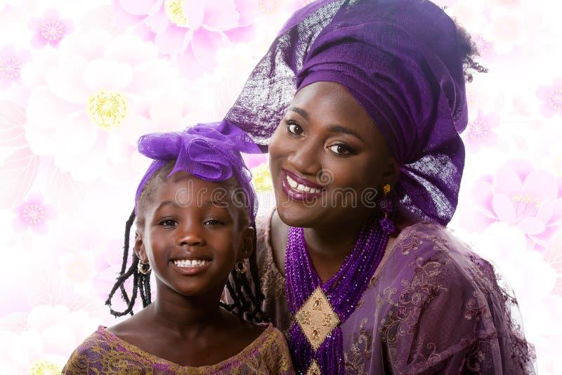 Stående av den härliga afrikanska damen och lilla flickan i traditionell klänning arkivfoto