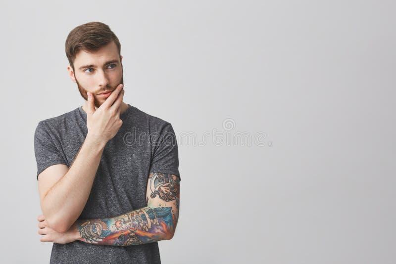Stående av den härliga allvarliga europeiska mannen med skägget och tatueringen på handen för arminnehav i framsida som åt sidan  fotografering för bildbyråer