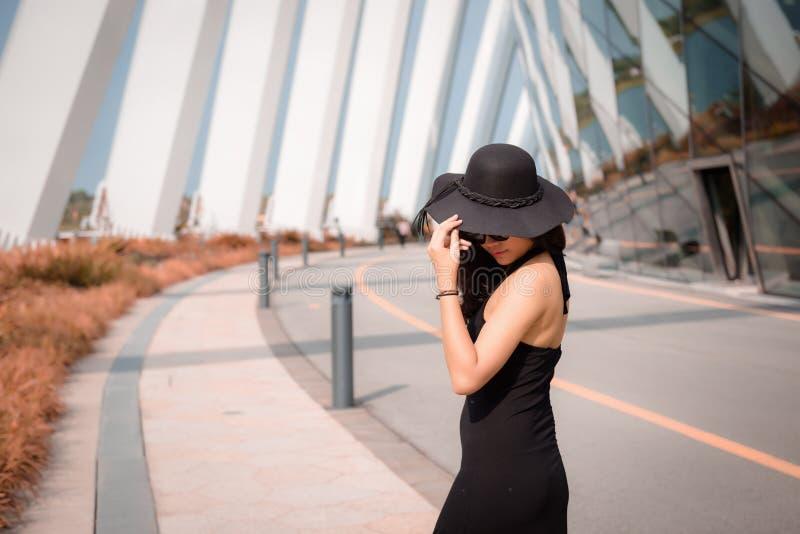 Stående av den härliga asiatiska kvinnan i svart klänning för mode med hennes hatt på fasadbyggnadsbakgrund, skönhet och modebegr royaltyfri bild