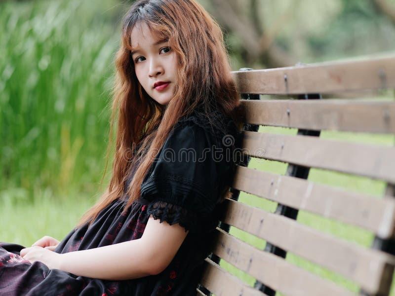 Stående av den härliga asiatiska kvinnan som sitter på bänk i sommarskogen, kinesisk flicka i den svarta klänningen för tappning  royaltyfri foto