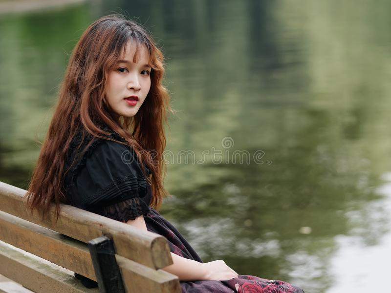 Stående av den härliga asiatiska kvinnan som sitter på bänk i sommarskogen, kinesisk flicka i den svarta klänningen för tappning  royaltyfria bilder