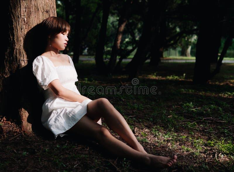Stående av den härliga asiatiska kvinnan som sitter under träd i sommarskogen, kinesisk flicka i den vita klänningen som sover me fotografering för bildbyråer