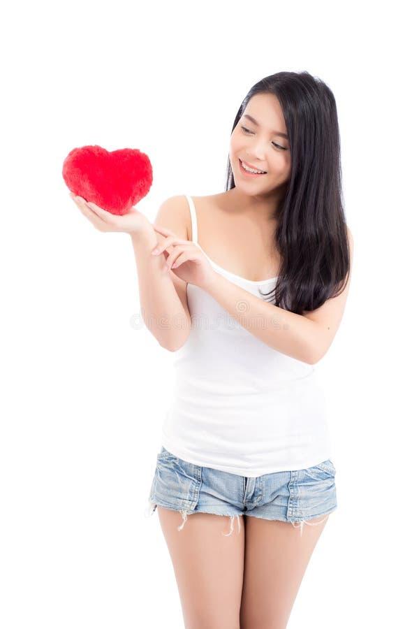 Stående av den härliga asiatiska unga kvinnan som rymmer och pekar den röda hjärtaformkudden och leende som isoleras på vit bakgr arkivfoton