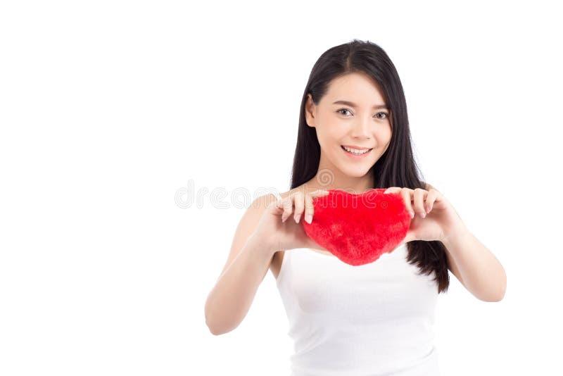 Stående av den härliga asiatiska unga kvinnan som rymmer den röda hjärtaformkudden och leende som isoleras på vit bakgrund, valen royaltyfria bilder