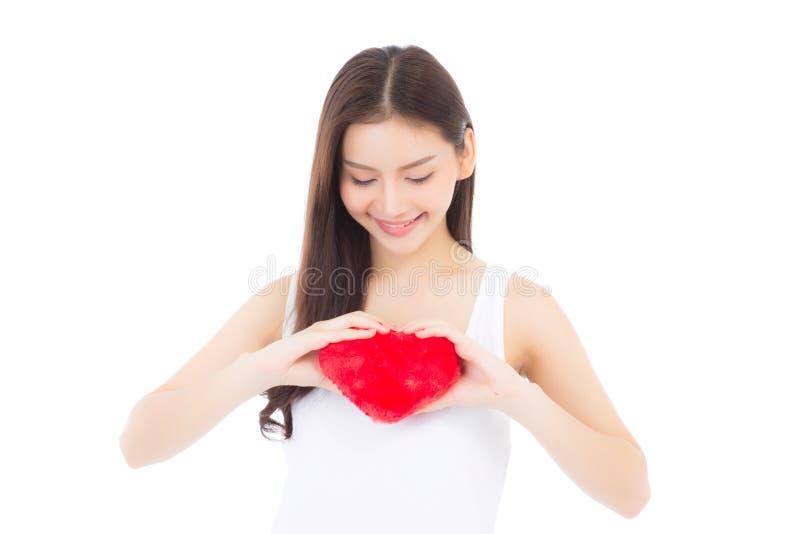 Stående av den härliga asiatiska unga kvinnan som rymmer den röda hjärtaformkudden och leende som isoleras på vit bakgrund arkivfoto