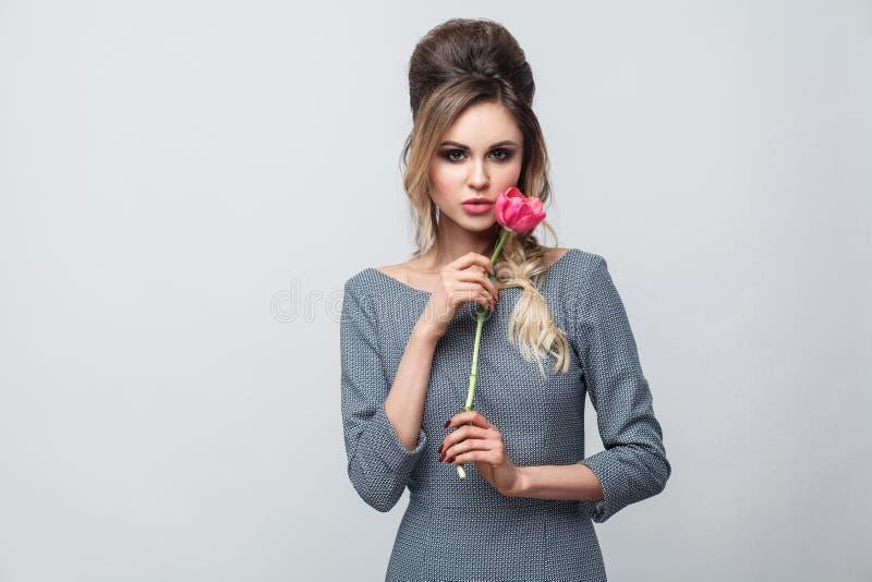 Stående av den härliga attraktiva modemodellen i grå klänning med makeup och frisyren och att stå, rymma den röda tulpan och seen royaltyfri foto