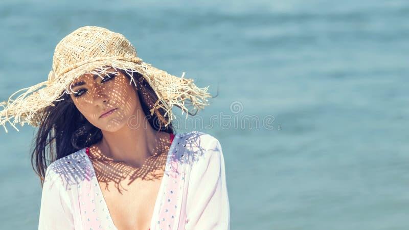 Stående av den härliga bärande sommarhatten för ung kvinna på stranden C royaltyfria bilder
