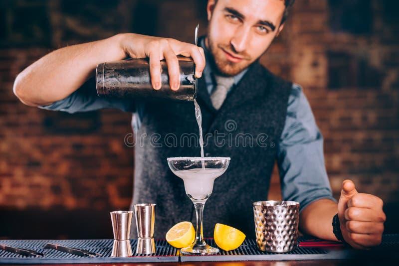Stående av den härliga bartendern som använder stånghjälpmedel för alkoholiserade coctailar Margarita med tequila, skiva av citro royaltyfri bild