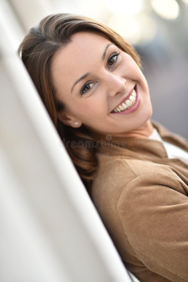 Stående av den härliga benägenheten för ung kvinna på stadsväggen arkivfoto