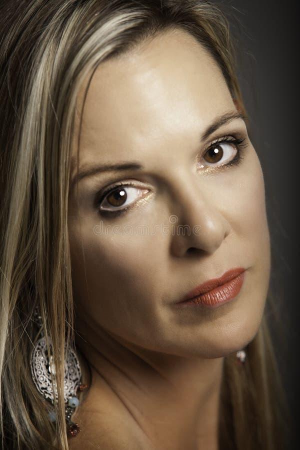 Stående av den härliga blonda äldre kvinnan med silverörhänget arkivfoto