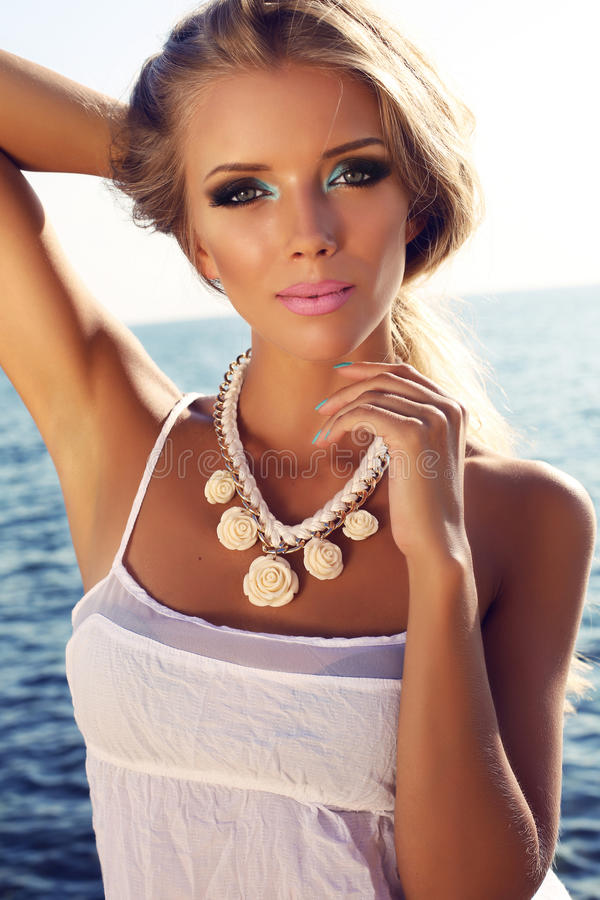 Stående av den härliga blonda flickan med ljus makeup som poserar på stranden royaltyfri foto