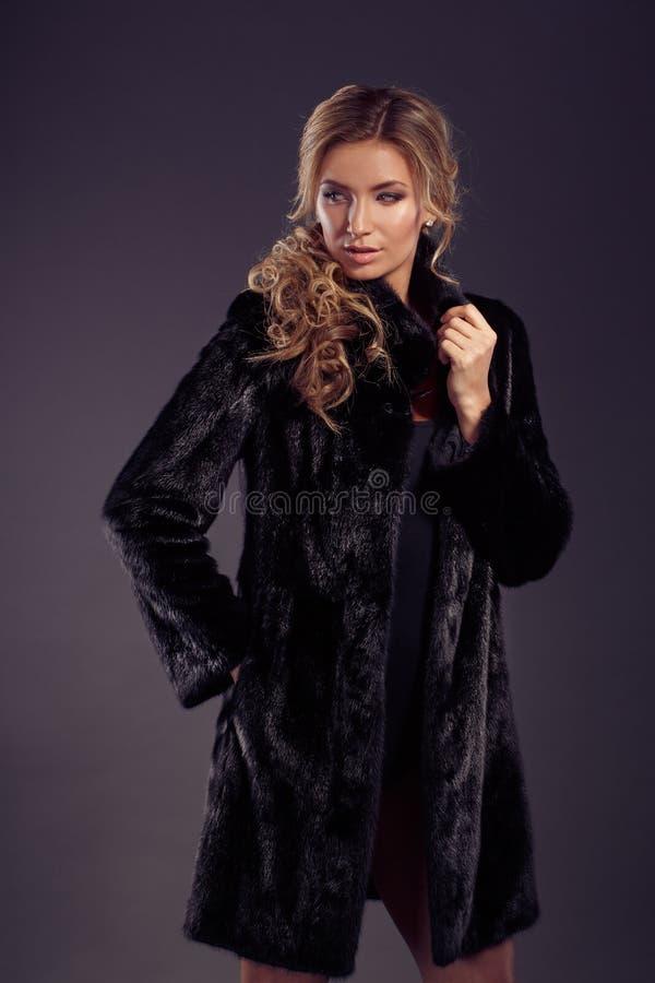 Stående av den härliga blonda kvinnan i svart pälslag fotografering för bildbyråer