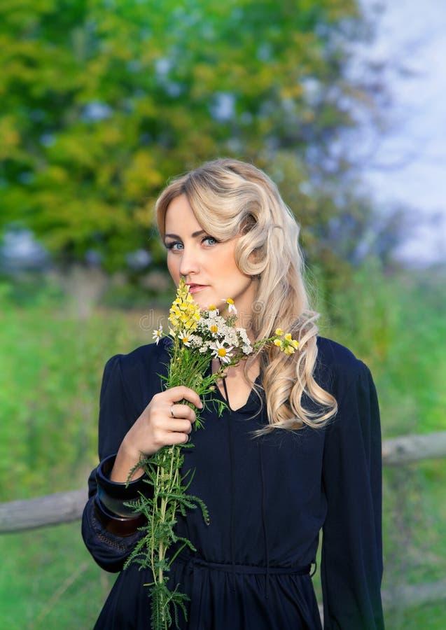 Stående av den härliga blonda kvinnan med buketten av den ljusa wildfloen arkivfoton