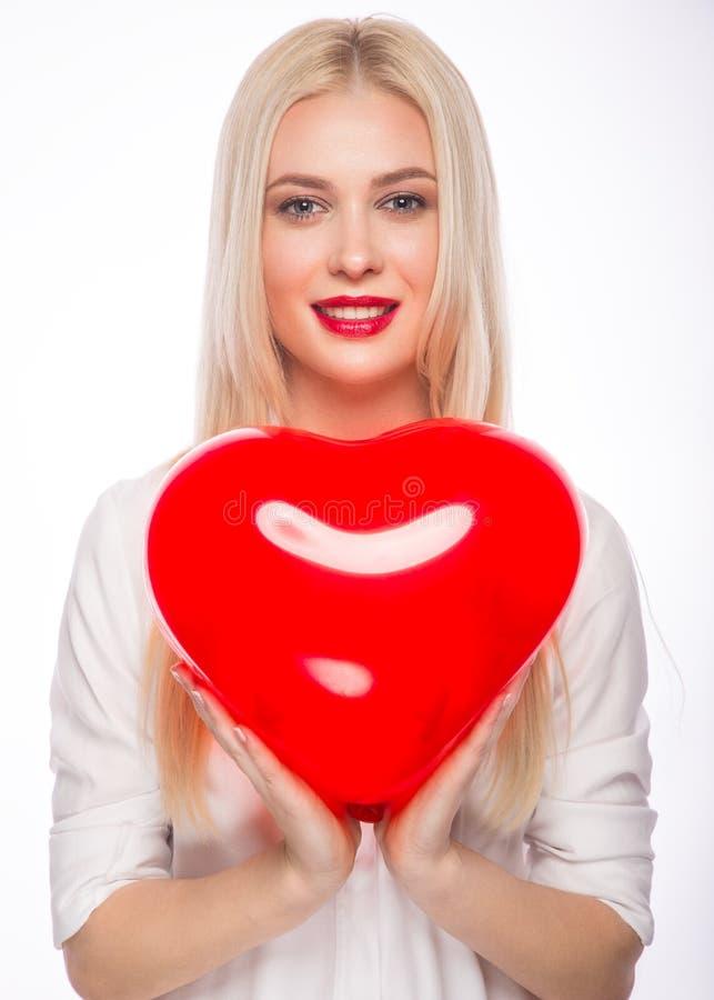 Stående av den härliga blonda kvinnan med ljus makeup och röd hjärta i hand red steg royaltyfri bild
