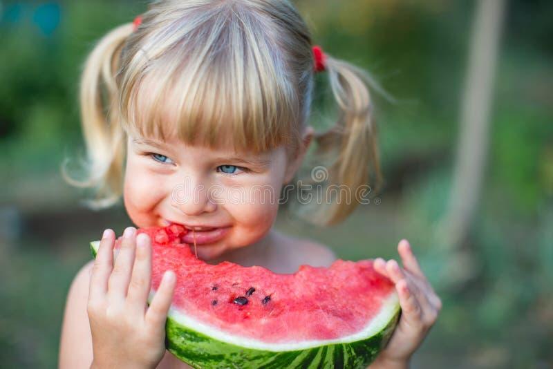 Stående av den härliga blonda lilla flickan med två hästsvansar som äter vattenmelon arkivfoton