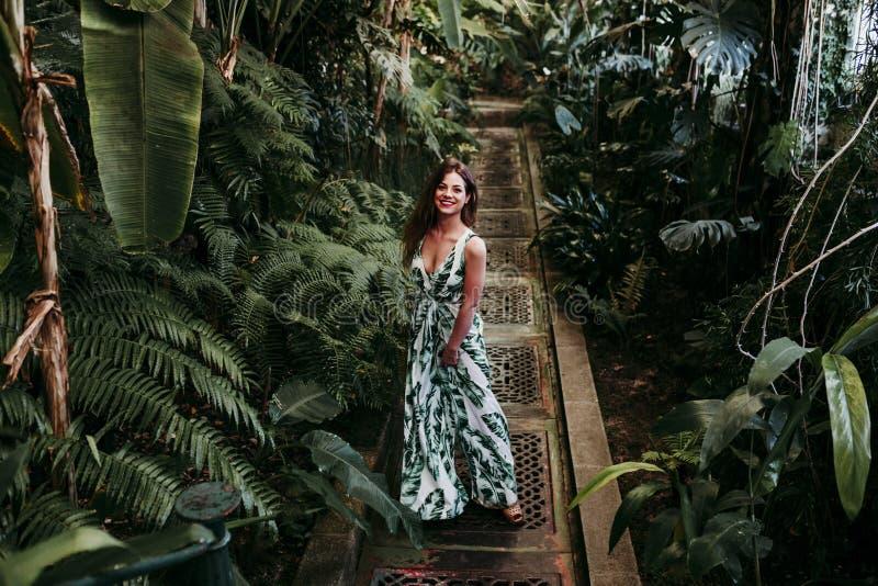 Stående av den härliga blonda unga kvinnan som ler på solnedgången i ett grönt hus som omges av tropiska växter Lycka och livssti royaltyfri foto