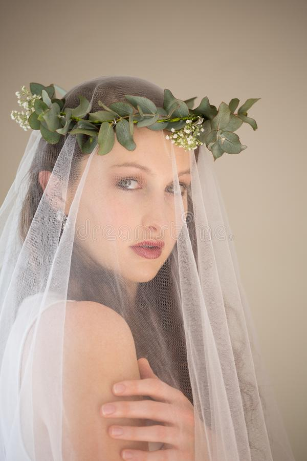 Stående av den härliga bruden i bröllopsklänning- och tiaraanseende vid väggen hemma royaltyfri foto