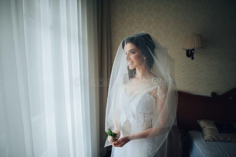 Stående av den härliga bruden i den vita klänningen royaltyfri foto