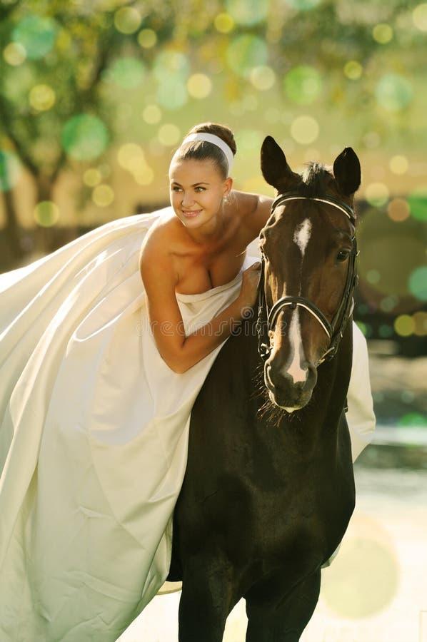 Stående av den härliga bruden med hästen arkivfoton