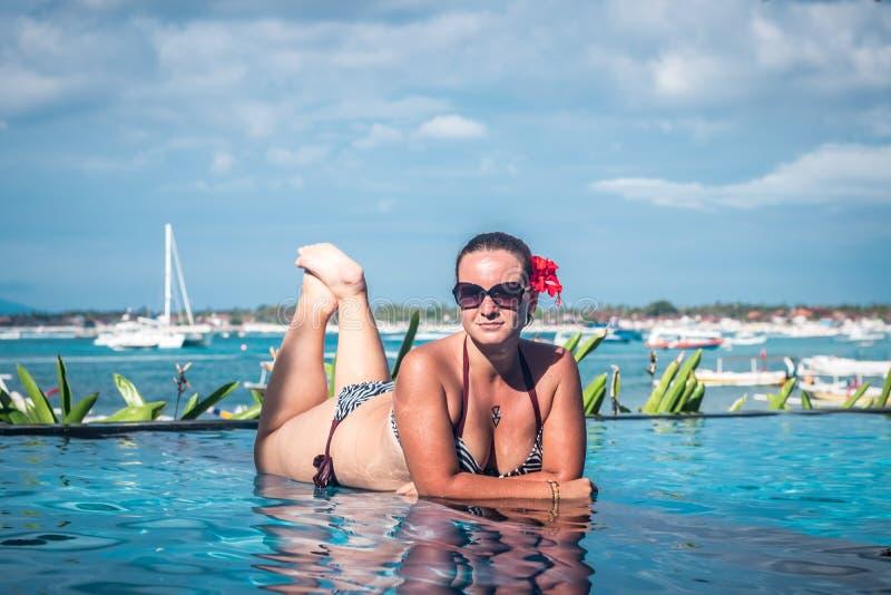 Stående av den härliga brunbrända kvinnan i svart swimwear som kopplar av i simbassängbrunnsort Varm sommardag och ljust soligt arkivbild