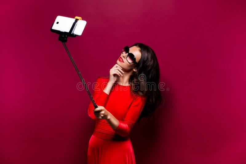 Stående av den härliga brunetten i enorm klänning och röda kanter som bär solglasögon, medan göra selfie med pinnen royaltyfri foto