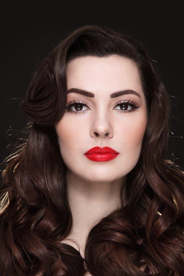 Stående av den härliga brunetten med lockigt hår och röd läppstift royaltyfri bild