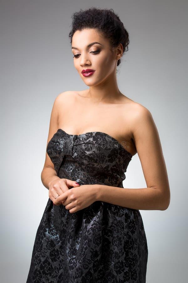 Stående av den härliga brunettflickan i studion på en grå bakgrund i klänning royaltyfri foto