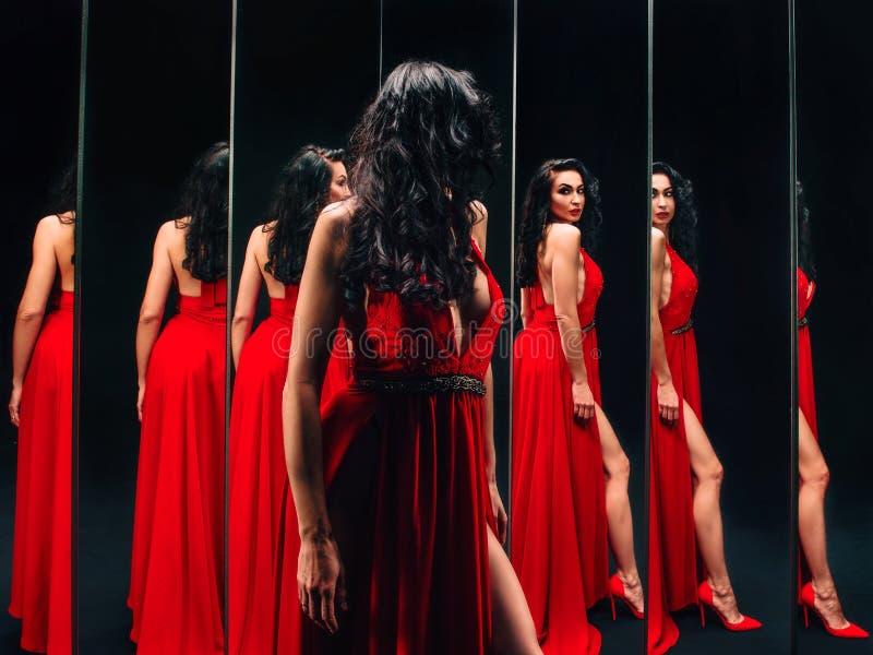 Stående av den härliga brunettkvinnan i röda skor och klänninganseende arkivfoto