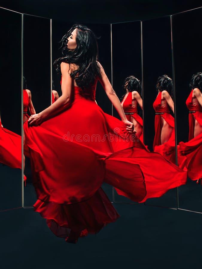 Stående av den härliga brunettkvinnan i röda skor och klänninganseende royaltyfri fotografi