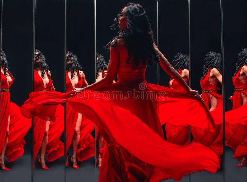 Stående av den härliga brunettkvinnan i röda skor och klänningen som omkring vänder och dansar arkivfoto