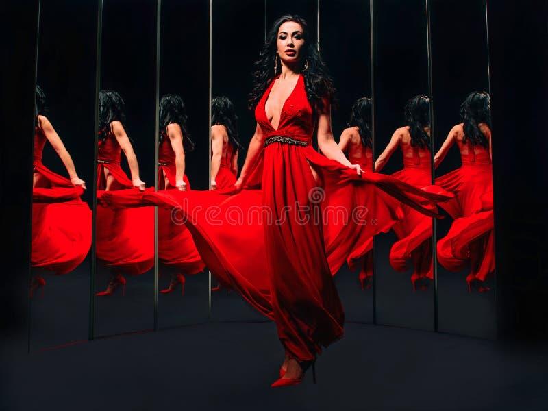 Stående av den härliga brunettkvinnan i röda skor och klänningen som omkring vänder och dansar arkivbilder