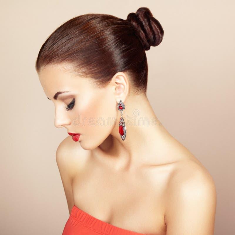 Stående av den härliga brunettkvinnan med örhänget. Perfekt makeu royaltyfria bilder