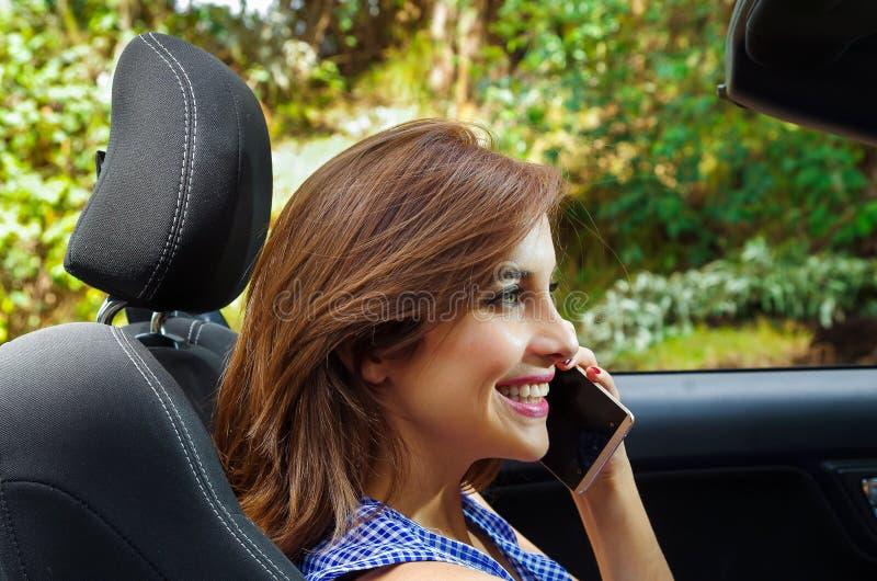 Stående av den härliga caucasian kvinnan som inom använder hennes mobiltelefon av den svarta bilen, medan hon kör i ett suddigt arkivbild