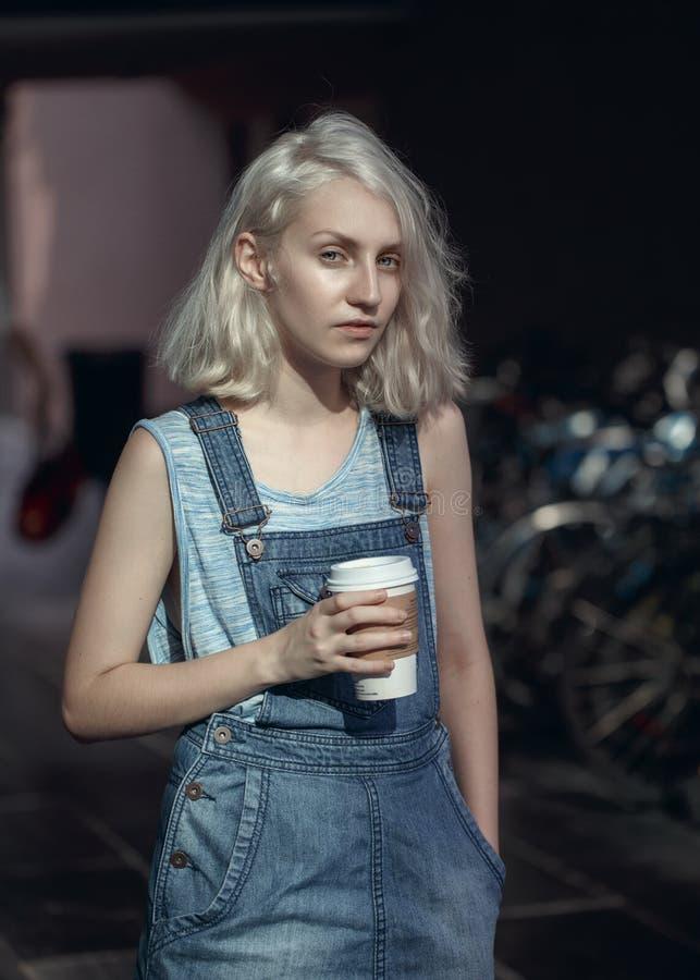 Stående av den härliga Caucasian tonårs- unga blonda flickakvinnan för alternativ modell i den blåa tshirten, jeansromper arkivbild