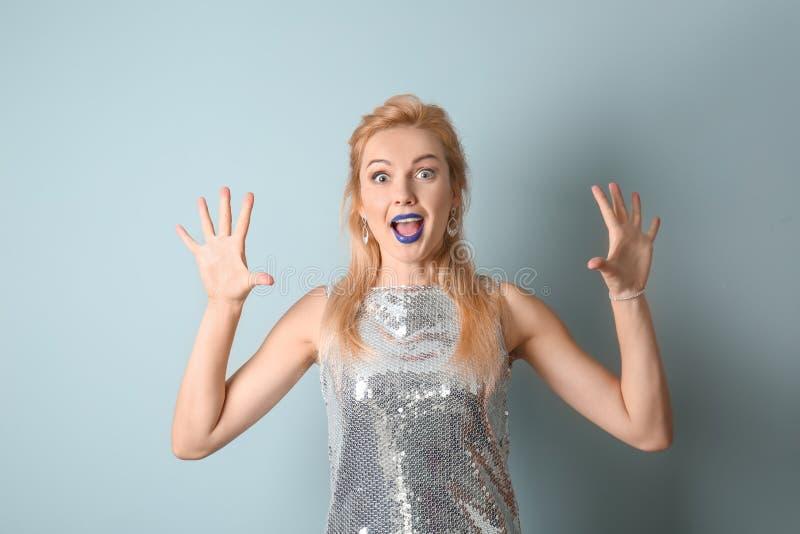 Stående av den härliga förvånade kvinnan med ovanlig läppstift på färgbakgrund arkivbild