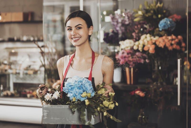 Stående av den härliga flickablomsterhandlaren i blomsterhandel royaltyfria bilder