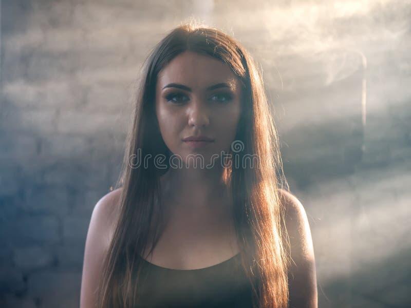 Stående av den härliga flickan i dimman arkivbilder