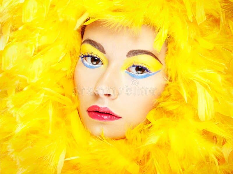 Stående av den härliga flickan i gula fjädrar. Perfekt makeup fotografering för bildbyråer