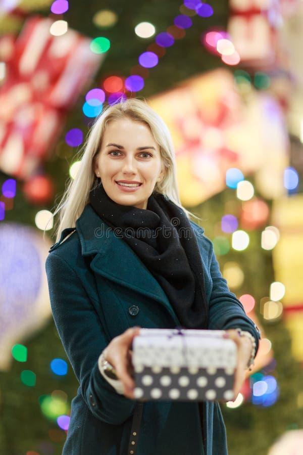 Stående av den härliga flickan i lag med gåvaasken på bakgrund av julgranen arkivfoton