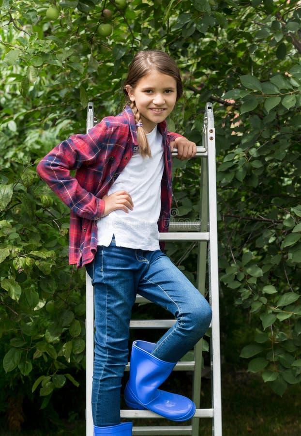 Stående av den härliga flickan i röd rutig skjorta och gummistöveler på trappstegen på trädgården royaltyfria foton