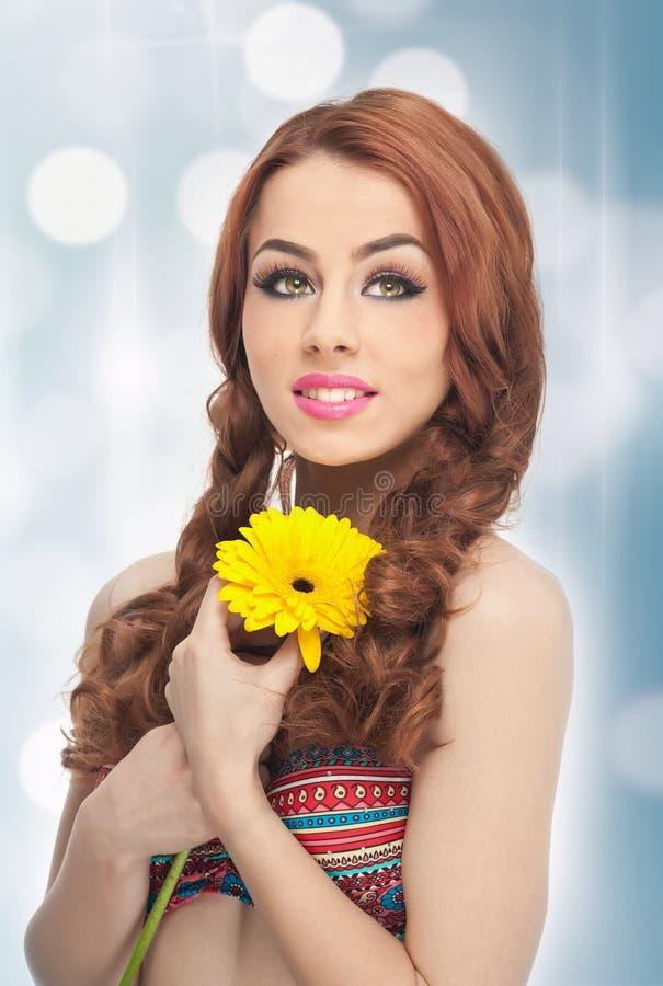 Stående av den härliga flickan i studio med den gula krysantemumet i henne händer Sexig ung kvinna med blåa ögon med den ljusa bl royaltyfri bild
