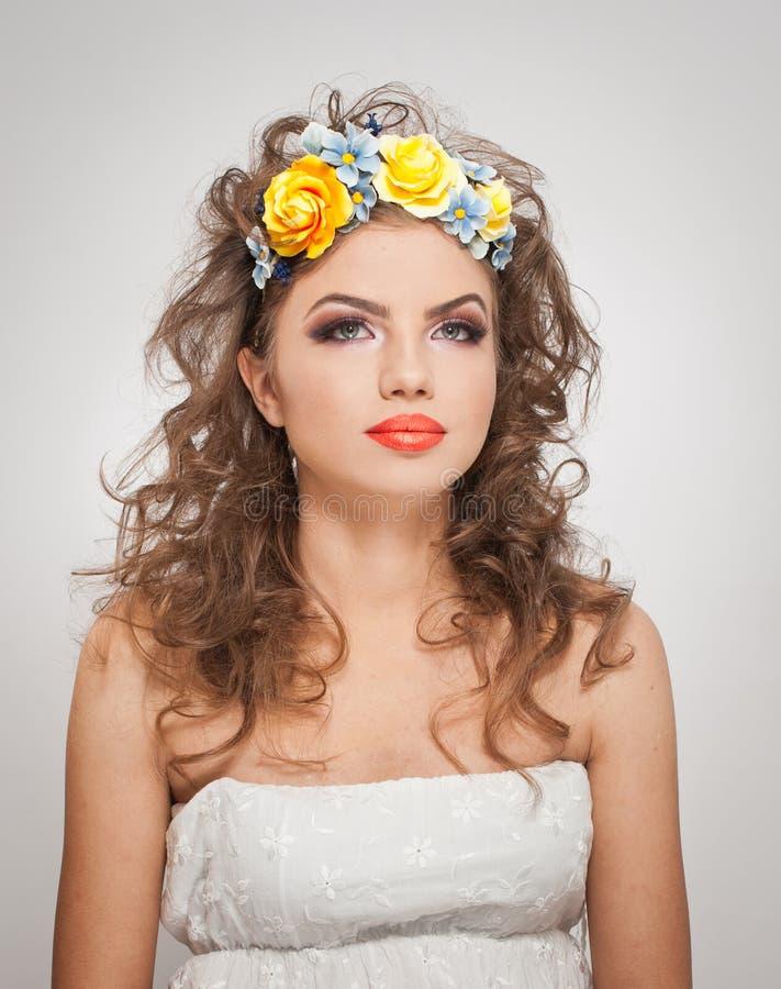 Stående av den härliga flickan i studio med gula rosor i hennes hår och nakna skuldror Sexig ung kvinna med yrkesmässig makeup royaltyfria foton