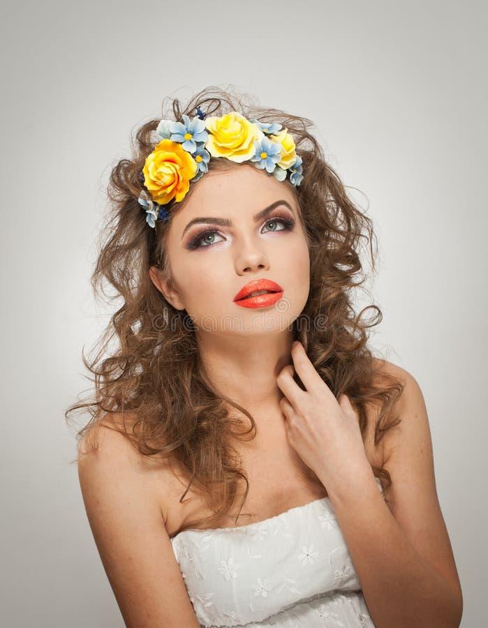 Stående av den härliga flickan i studio med gula rosor i hennes hår och nakna skuldror Sexig ung kvinna med yrkesmässig makeup arkivfoto