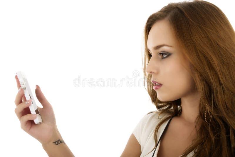 Stående av den härliga flickan med den moderna mobiltelefonen i handisola fotografering för bildbyråer