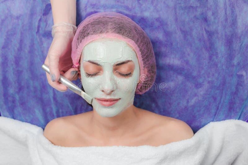 Stående av den härliga flickan som applicerar ansikts- behandlingar för leramaskeringsskönhet royaltyfri foto