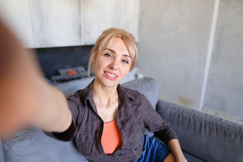 Stående av den härliga flickan som rymmer kameran på den långsträckta handen royaltyfri bild