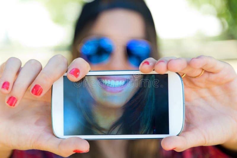 Stående av den härliga flickan som tar en selfie med mobiltelefonen arkivbild