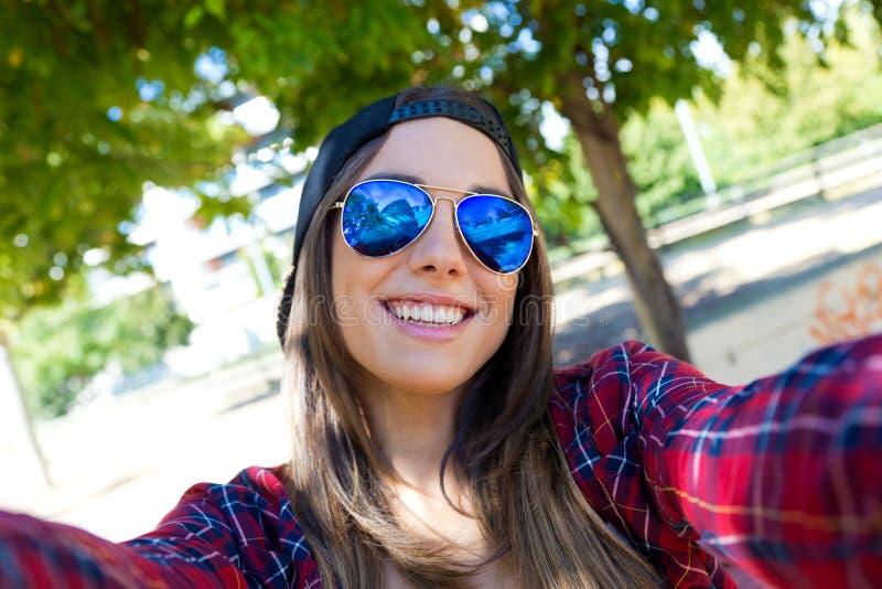 Stående av den härliga flickan som tar en selfie med mobiltelefonen arkivfoton